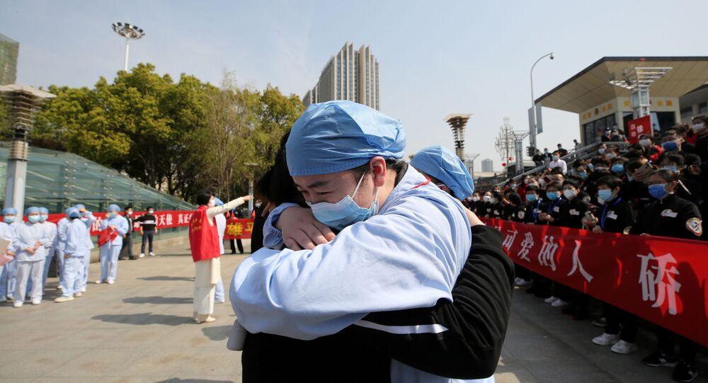 Médico chinês se despede de colega antes de voltar para a sua província natal, na Estação Ferroviária de Wuhan, em 20 de março de 2020