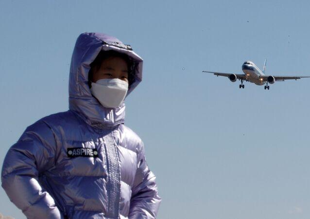 Estudante usando máscara protetora posa para foto perto do Aeroporto Internacional de Pequim, na China, 13 de março de 2020