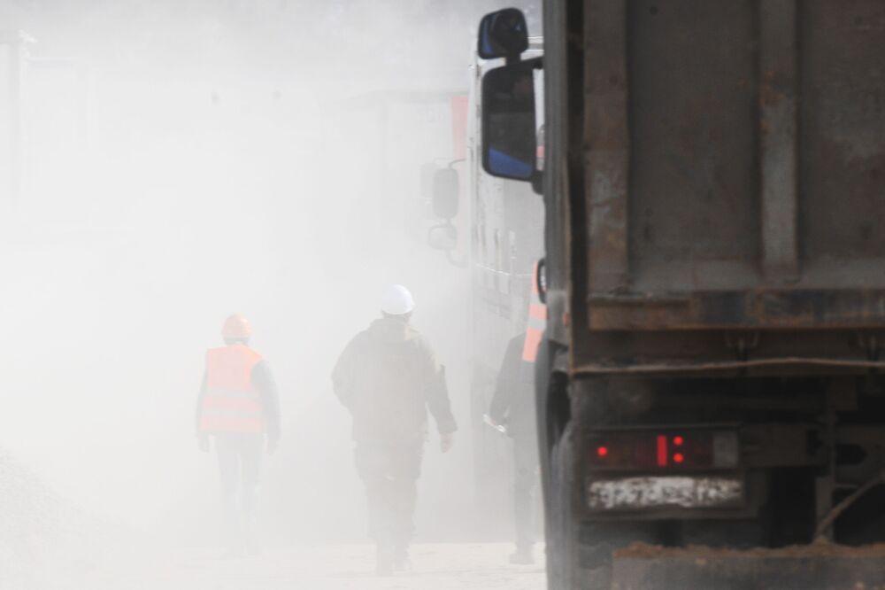 Trabalhadores e nuvem de poeira levantada por caminhões no canteiro de obras do novo hospital de infectologia