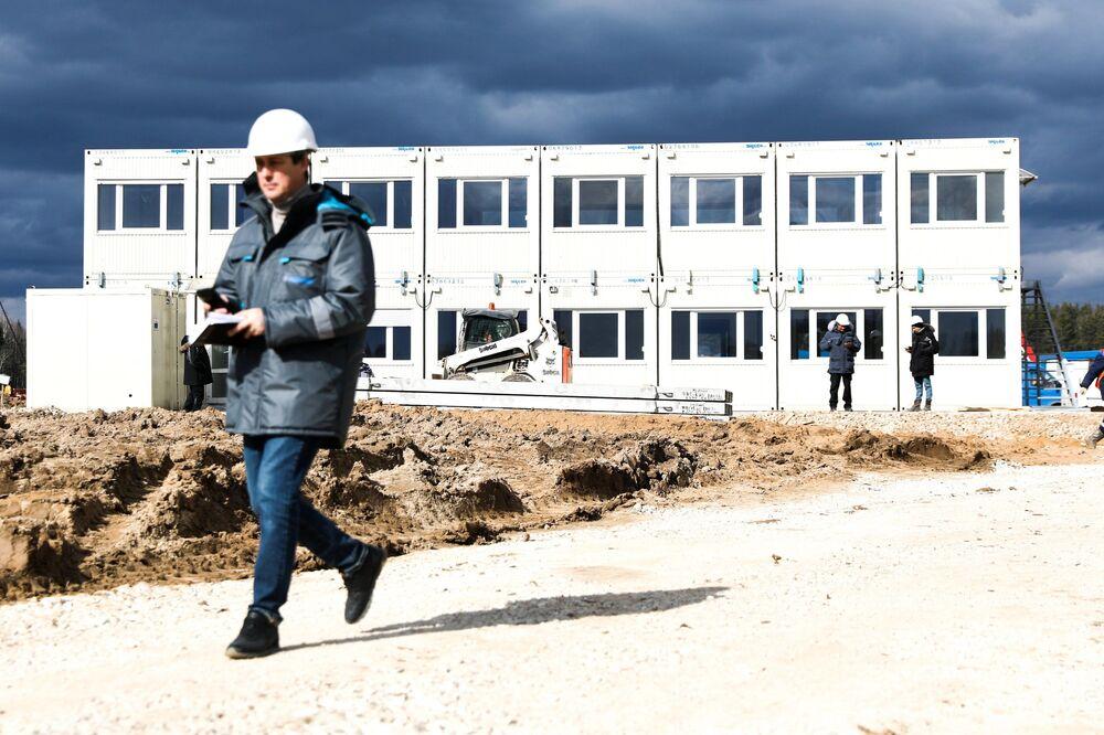 Trabalhador passa em frente de uma das instalações em construção