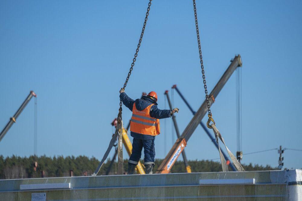 Trabalhador ajudando no processo de instalação de viga