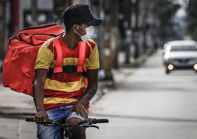 Entregador de aplicativo de fast food é visto circulando pela avenida Caxanga no bairro da Iputinga, na zona central da cidade de Recife (PE), neste domingo (22).