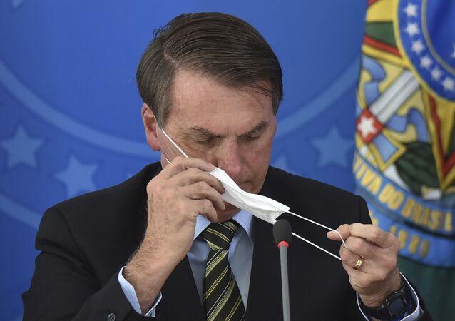 Jair Bolsonaro coloca uma máscara durante coletiva no Palácio do Planalto