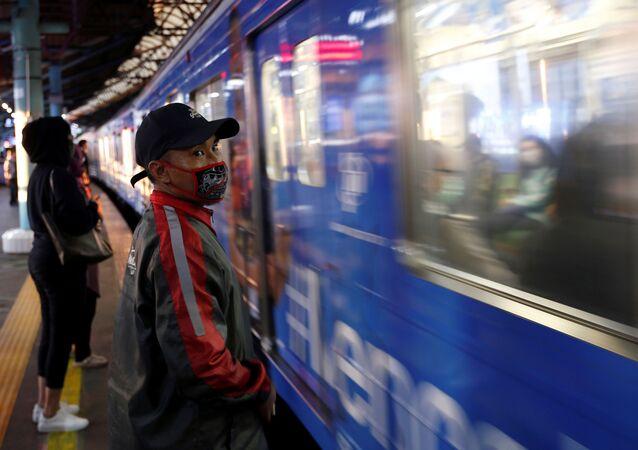 Passageiro com máscara facial espera enquanto um trem suburbano passa em uma estação em meio à propagação da COVID-19 em Jacarta, Indonésia, 2 de abril de 2020 (imagem referencial)