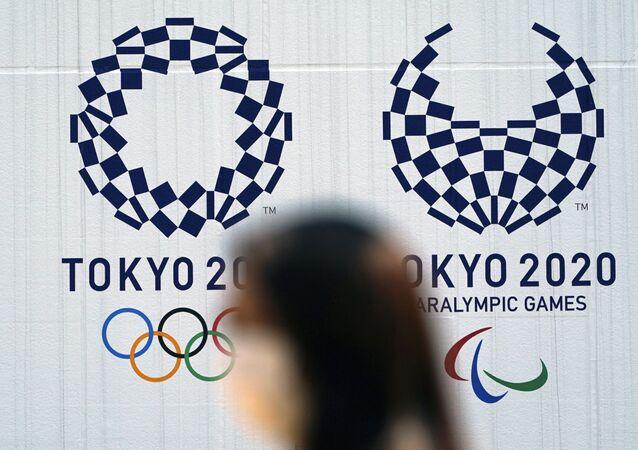 Mulher com máscara passa diante de logo das Olimpíadas de Tóquio, em 1º de abril de 2020