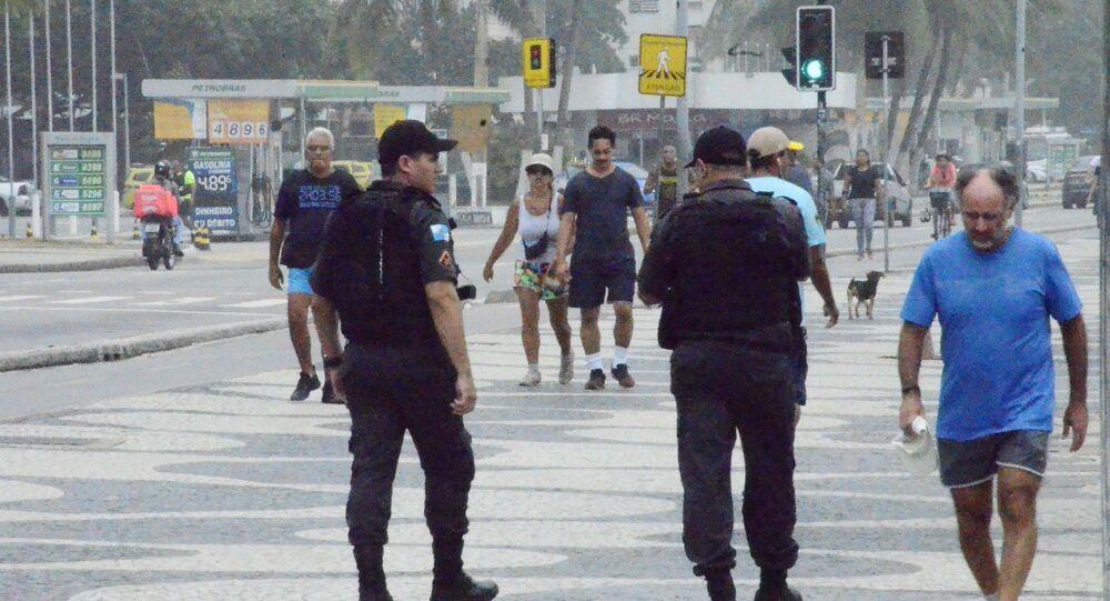 Pedestres caminham na praia de Copacabana, no Rio de Janeiro (RJ), mesmo com quarentena devido à epidemia do coronavírus