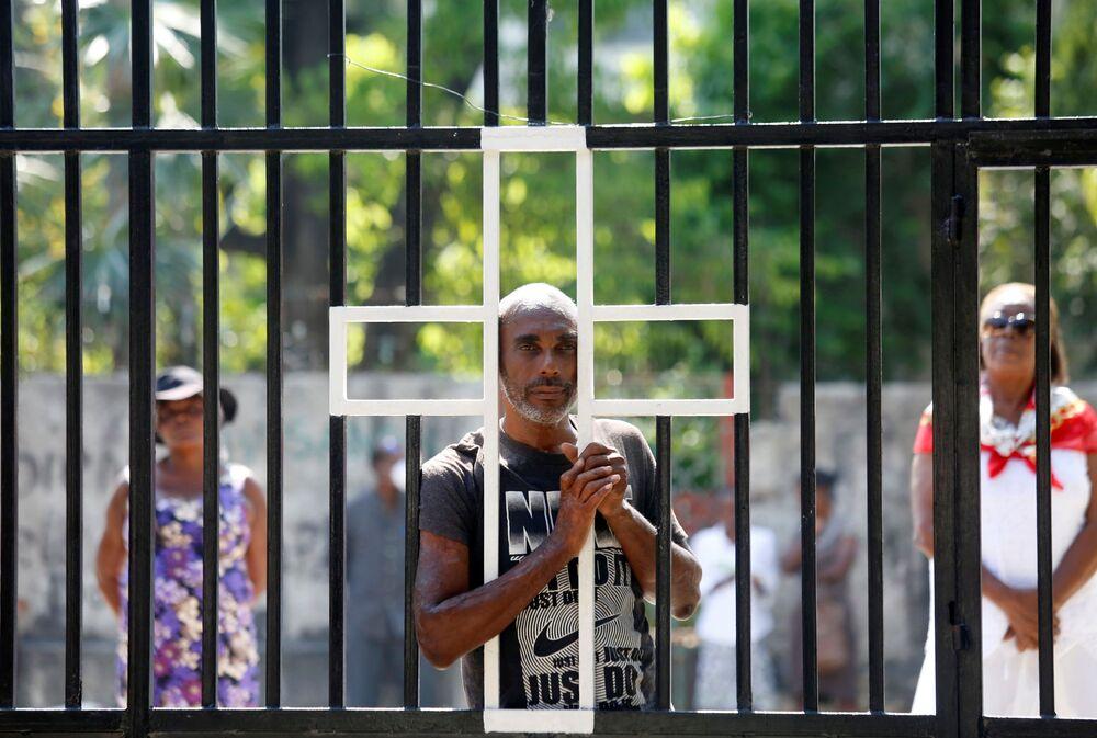 Fiéis ficam em frente a uma igreja fechada ao público no Domingo de Páscoa devido à pandemia em Porto Príncipe, Haiti