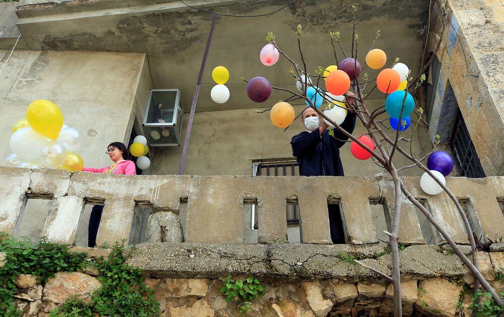Homem prende balões a uma árvore no Líbano para celebrar a Páscoa na cidade de Jezzine em 12 de abril de 2020