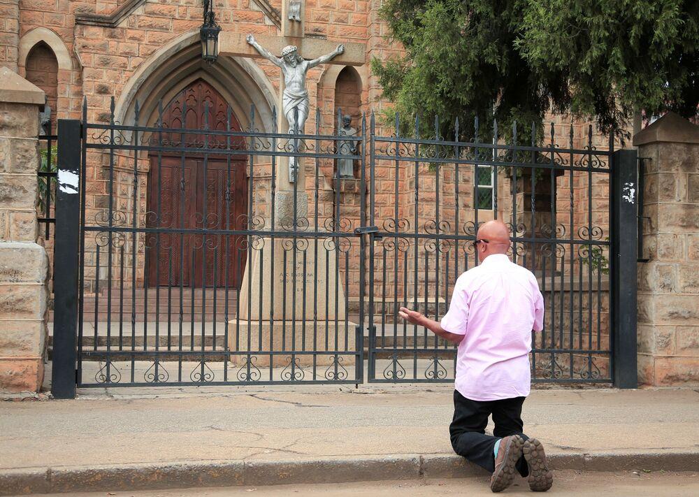 Fiel ora do lado de fora de uma igreja no Domingo de Páscoa durante quarentena de 21 dias em Harare, no Zimbábue