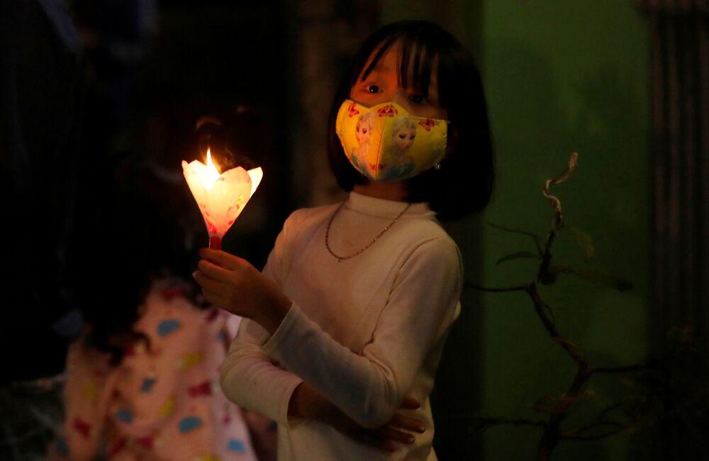 Menina usa máscara durante celebração no Domingo de Páscoa em sua casa na província vietnamita de Vinh Phuc