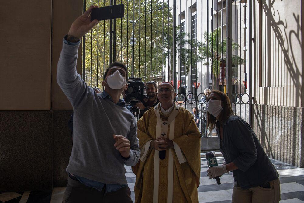 Jornalistas tiram fotos com o cardial uruguaio Daniel Sturla depois da missa de Páscoa em uma igreja vazia