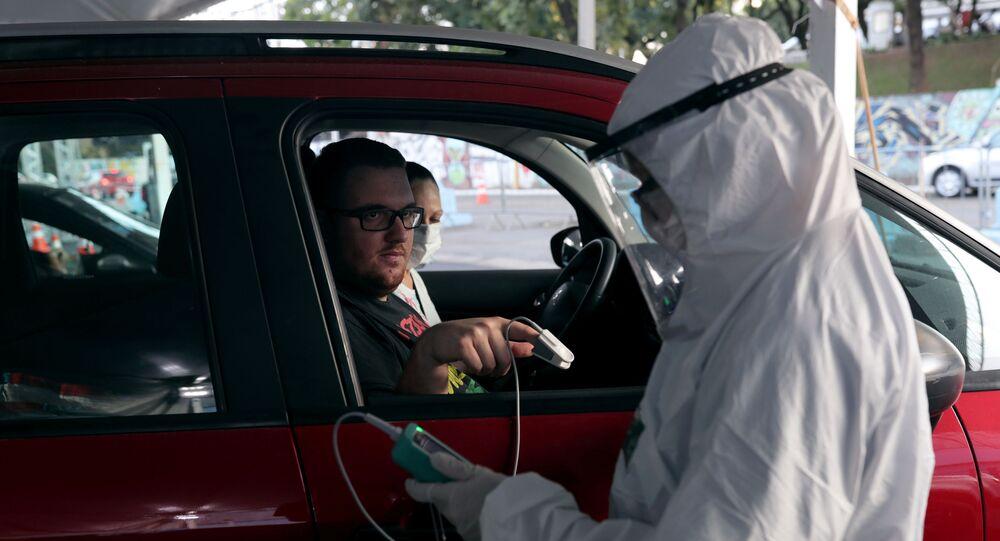 Enfermeira mede o nível de oxigênio do sangue de um homem para identificar pessoas com COVID-19, Guarulhos, SP, 3 de abril