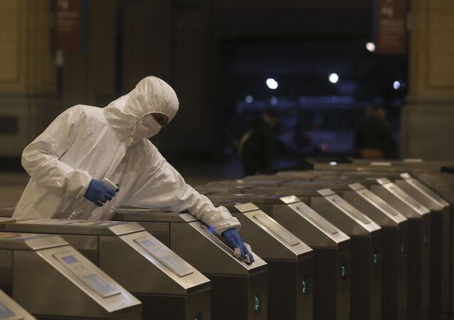 Funcionário com traje de proteção realiza limpeza de metrô na capital argentina, Buenos Aires