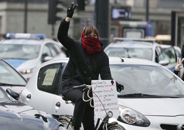 Mulher de máscara participa de protesto conta restrições ao aborto na Polônia.