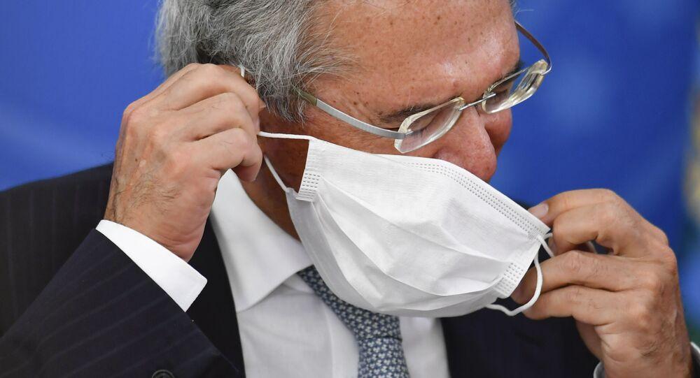 O ministro da economia coloca uma máscara para se proteger da COVID-19 durante coletiva de imprensa em Brasília.