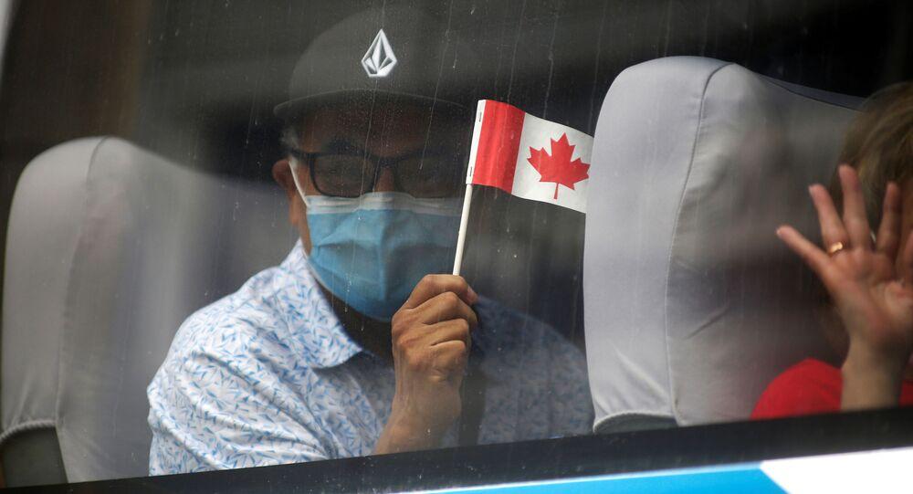 Homem de máscara segurando bandeira do Canadá em um ônibus para voos de repatriação organizados pela embaixada do Canadá no Peru em meio à pandemia do novo coronavírus