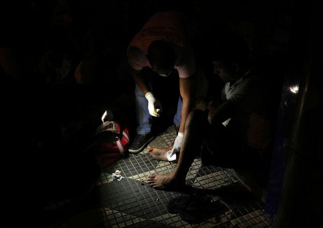 Voluntário trata o pé machucado de um morador de rua em meio à pandemia do coronavírus, no centro de São Paulo, Brasil, 28 de março de 2020