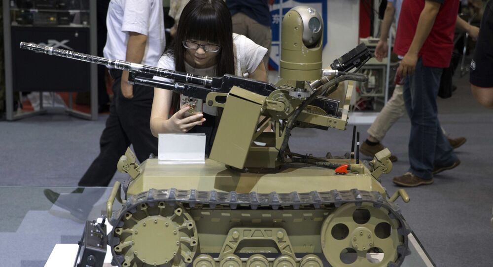 Visitante tira foto de um robô armado controlado à distância em Exposição Internacional na China