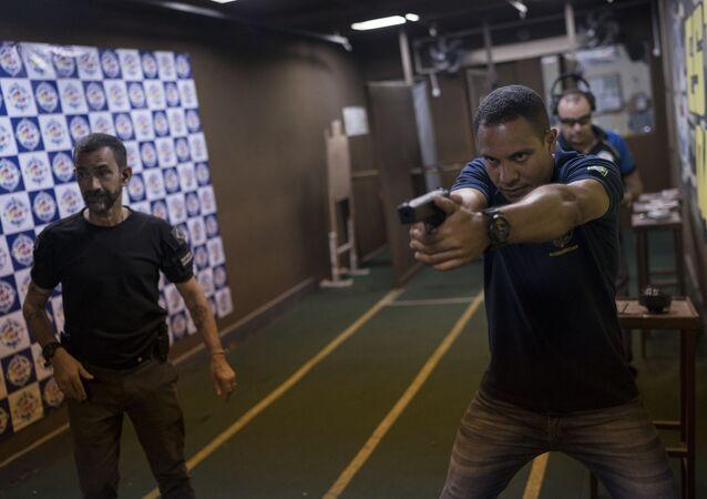 Homens praticam tiro em estande localizado em São Gonçalo, no Rio de Janeiro.