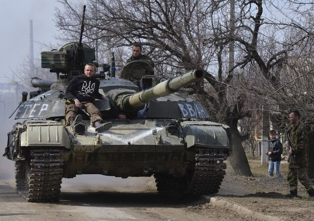 Members of the Ukrainian armed forces drive a tank in the settlement of Luhanske, Donetsk region, March 27, 2015