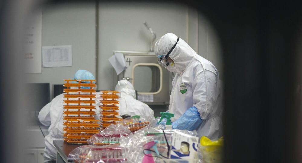 Laboratório na China em que profissionais de saúde realizam testes para identificar pacientes com coronavírus