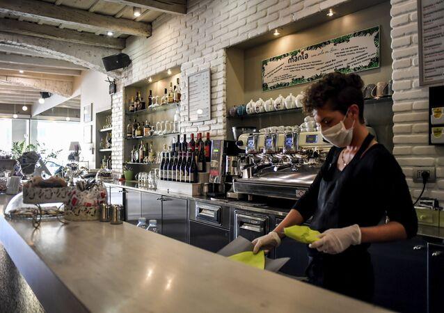 Atendente com máscara para se proteger do coronavírus organiza balcão de restaurante na Lombardia, no norte da Itália