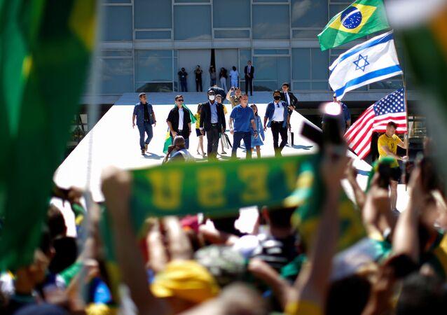 O presidente do Brasil, Jair Bolsonaro, cumprimenta apoiadores durante um protesto pedindo intervenção militar em Brasília, no dia 3 de maio de 2020.