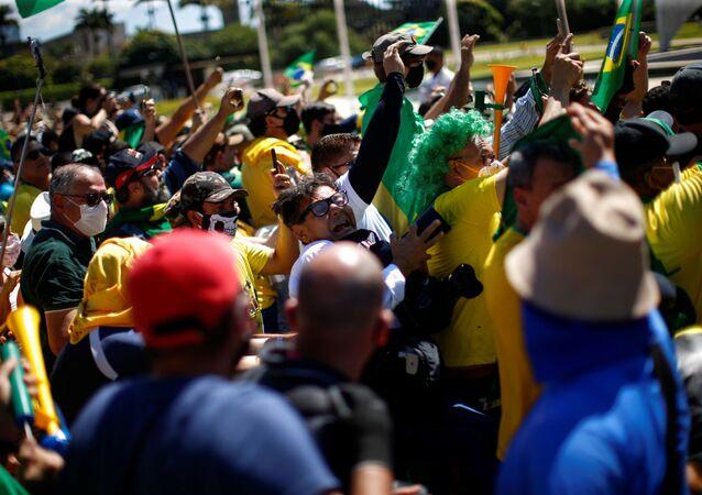 O fotojornalista Dida Sampaio (ao centro com uma câmera na mão e óculos) é empurrado de uma escada e agredido por apoiadores de Jair Bolsonaro.