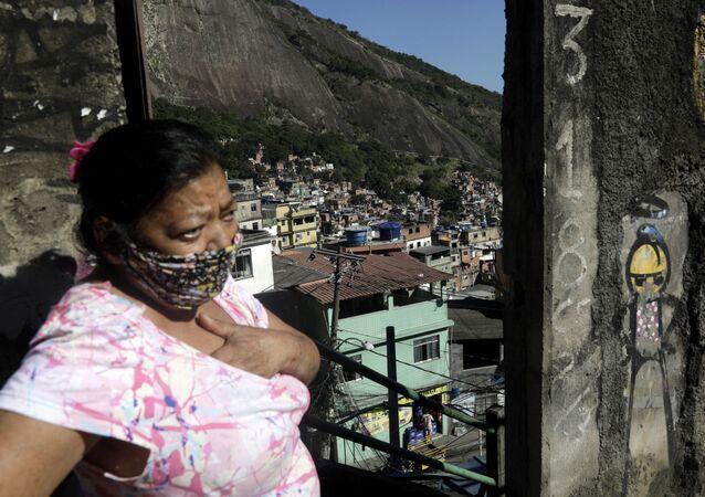 Mulher usando máscara na Rocinha, Rio de Janeiro, durante pandemia de coronavírus.