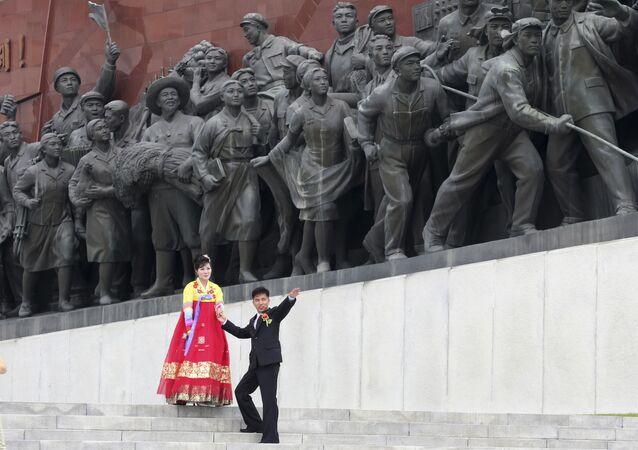 Casal diante de monumento em Pyongyang, na Coreia do Norte