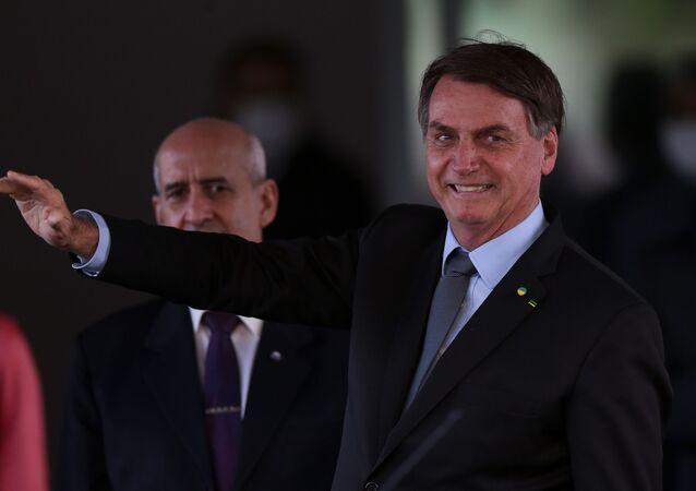 Presidente Jair Bolsonaro acena para apoiadores ao sair do Ministério da Defesa, em Brasília