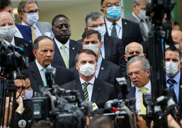 Em Brasília, presidente do Brasil, Jair Bolsonaro, usa máscara ao falar com a imprensa em meio a membros de seu governo após uma reunião com o presidente do Supremo Tribunal Federal (STF), Dias Toffoli.