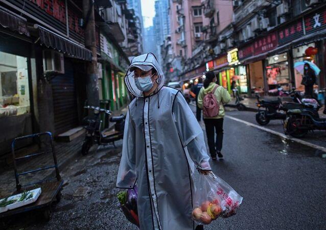 Pedestre levando bolsas de compras em Wuhan, China (foto de arquivo)