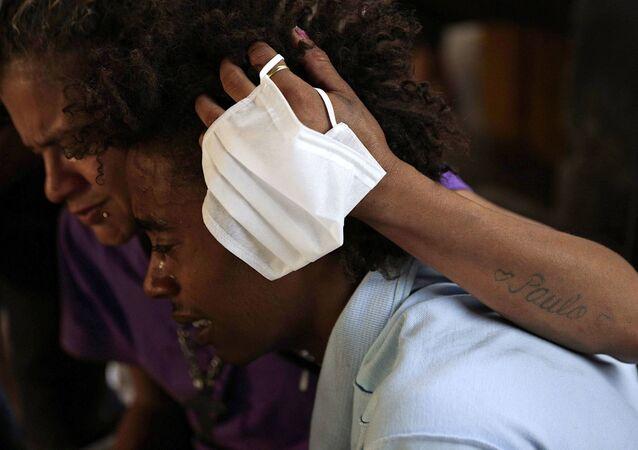 Um casal chora enquanto membros do projeto Fala Comigo! rezam e tocam música gospel enquanto oferecem máscaras e comida na área conhecida como Cracolância, região central de São Paulo, em meio à pandemia da COVID-19.