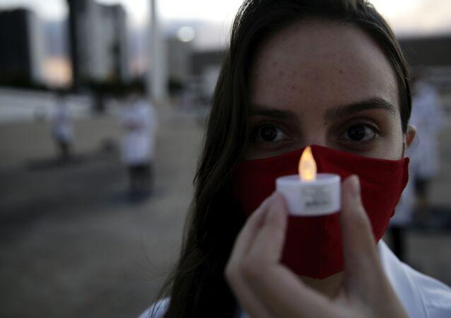 Enfermeira segura vela em homenagem a colega que morreu de COVID-19 durante a pandemia durante um protesto em Brasília.