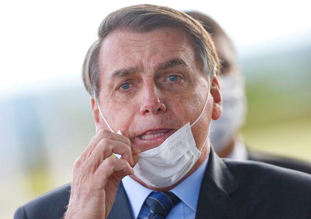 Presidente do Brasil, Jair Bolsonaro, ajusta sua máscara ao deixar o Palácio da Alvorada, em Brasília, 13 de maio de 2020