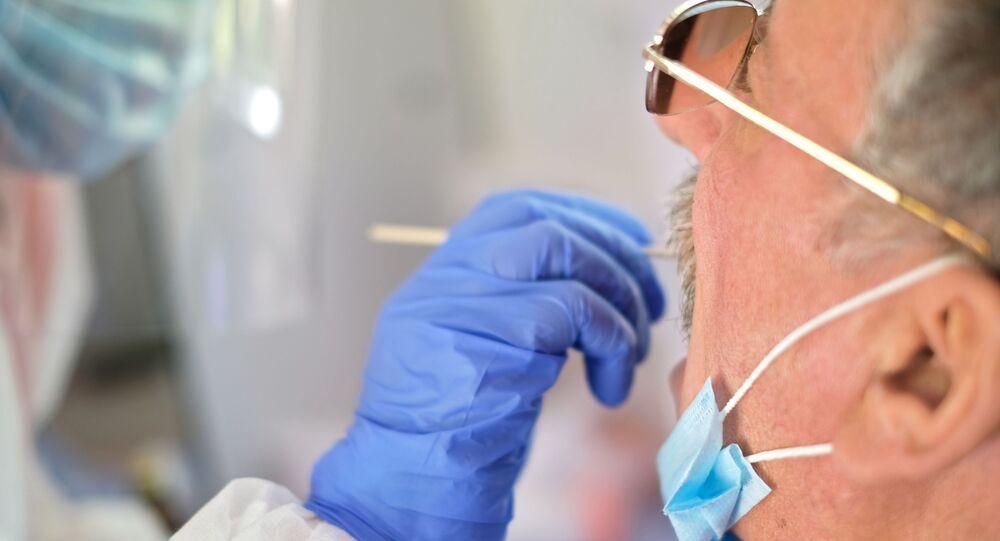 Funcionário da saúde de uma estação móvel de testes de coronavírus retira amostra de um paciente na vila de Enem, na república russa da Adigueia