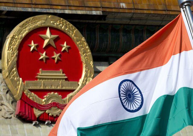 Bandeira da Índia ao lado do brasão nacional da China, em Pequim