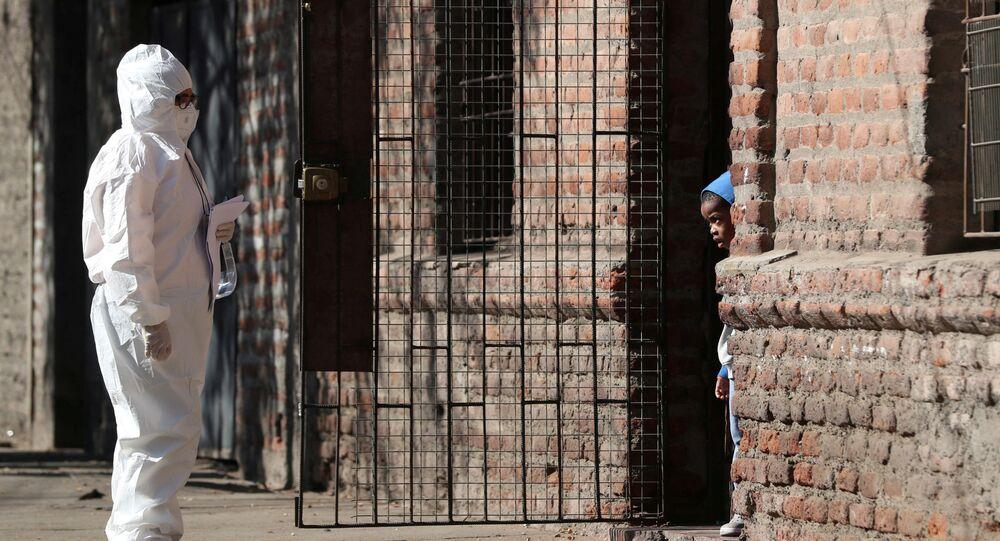 Mulher vestindo traje de proteção contra coronavírus conversa com criança em um bairro de migrantes em Santiago, Chile, 16 de maio de 2020