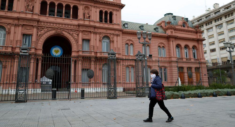 Uma mulher usando máscara contra a COVID-19 caminha em frente à Casa Rosada, em Buenos Aires, Argentina, em 21 de maio de 2020.