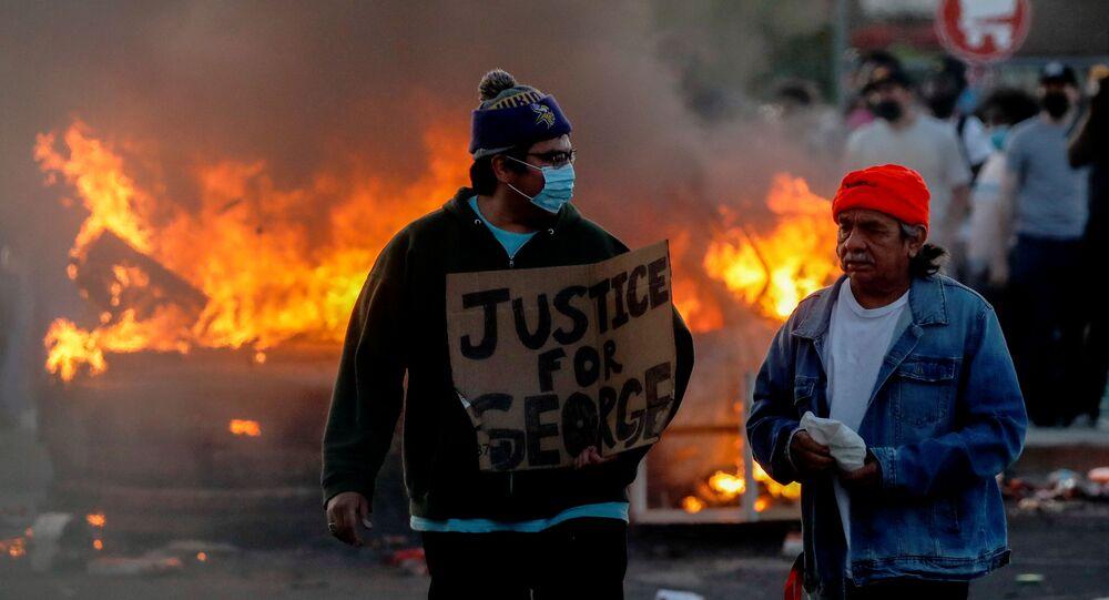 Manifestantes carregam um cartaz em Minneapolis pedindo justiça para George Floyd