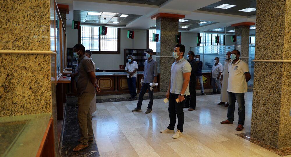 Líbios com máscaras protetoras estão na fila, enquanto mantém o distanciamento social em meio à pandemia da COVID-19, no North Africa Bank, na cidade de Janzour, Trípoli, Líbia, 10 de junho de 2020