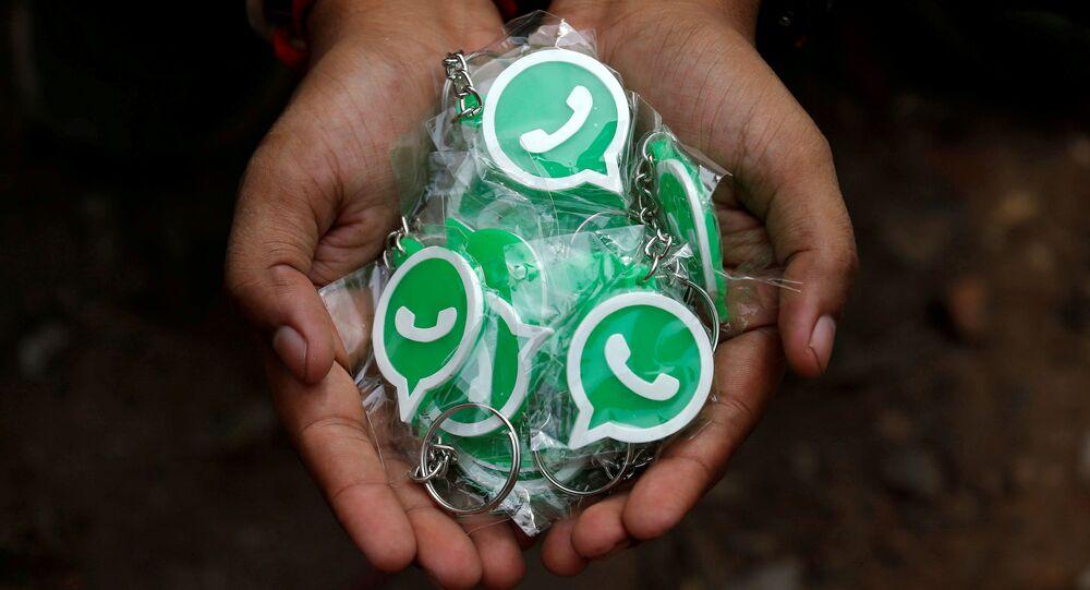 Representante do WhatsApp com a companhia de telecomunicações Reliance Jio exibe chaveiros com o logotipo do WhatsApp para distribuição durante uma campanha das duas empresas para educar usuários, nos arredores de Calcutá, Índia, 9 de outubro de 2018