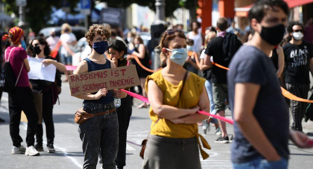 Em Berlim, manifestante segura uma placa com a frase, em alemão, racismo é a pior pandemia, durante protesto antirracista em 13 de junho de 2020.