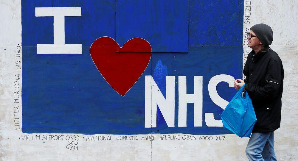 Em 12 de junho de 2020, em Manchester, um homem caminha em frente a um grafitti com a inscrição, em inglês, eu amo o NHS, em homenagem ao sistema público de saúde britânico, em meio à pandemia da COVID-19.