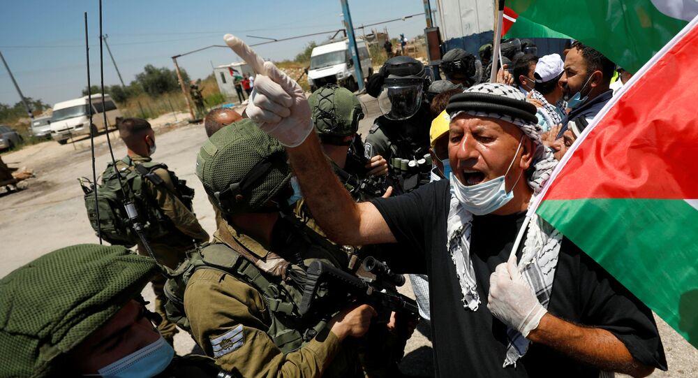 Palestino protesta diante de forças israelenses em ato contra a anexação da Cisjordânia por Tel Aviv