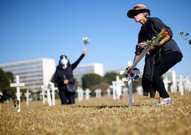 Em Brasília, uma ativista se agacha com flores nas mãos em meio a cruzes que simbolizam os mortos pela COVID-19 durante protesto contra o presidente brasileiro, Jair Bolsonaro, em 28 de junho de 2020, em frente ao Congresso Nacional.