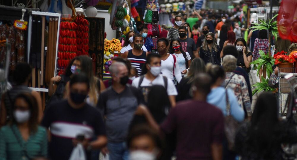 Pessoas andam em rua comercial popular, após flexibilização das restrições implantadas pelo coronavírus no Rio de Janeiro, Brasil, 29 de junho de 2020