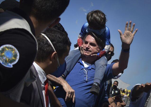 Presidente Jair Bolsonaro carrega uma criança em suas costas em ato a favor do seu governo em Brasília