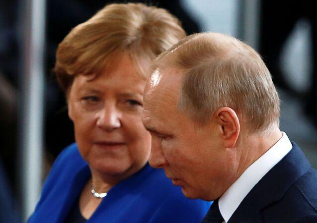 A chanceler alemã Angela Merkel conversa com o presidente russo Vladimir Putin ao chegar para a cúpula da Líbia em Berlim, Alemanha, 19 de janeiro de 2020